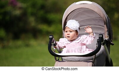 Little cute baby-girl sitting in the baby carriage. Little...