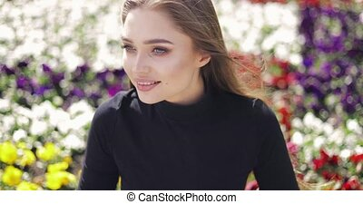 Beautiful woman posing on background of flowers - Gentle...