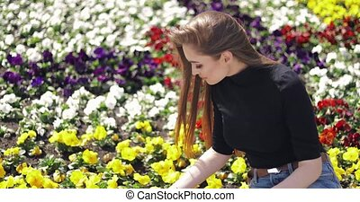 Female posing with flowers on ground - Side view of female...