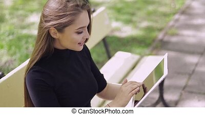 Beautiful girl browsing tablet - Side view of female with...