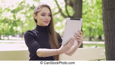Smiling woman using tablet in park - Smiling beautiful woman...