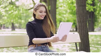 Smiling woman using tablet - Young smiling woman in casual...