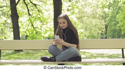 Tender female with phone on bench - Casual pretty female...