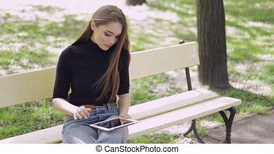 Cheerful young woman using tablet outside - Beautiful young...