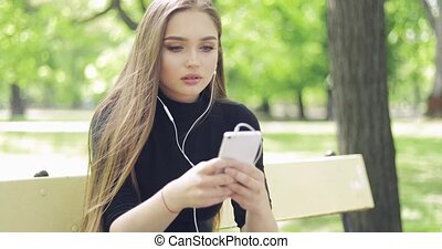 Pretty female with smartphone on bench - Pretty young woman...