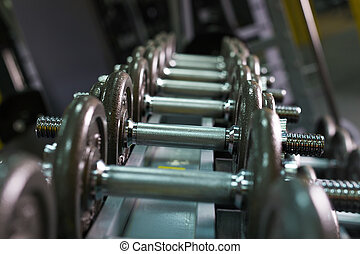 Rows of dumbbells in the gym. Rows of metal dumbbells on...