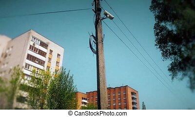 CCTV camera hanging on a pole on blue sky background.