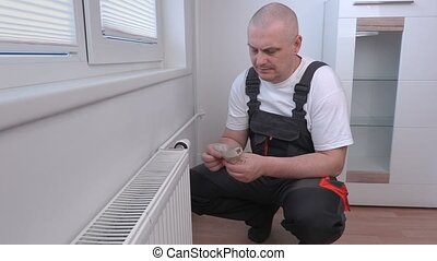 Man counting money near radiator