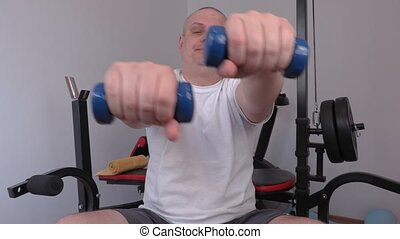 Tired man doing exercise with two small dumbbells