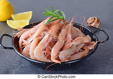 Raw fresh shrimps in a black metal bowl with rosemary on a...