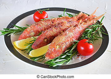 Grilled red mullet in a plate with herbs, tomato and lemon....
