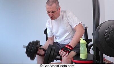 Man doing exercise with dumbbell for biceps