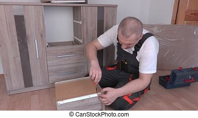 Man with screwdriver mounted drawer