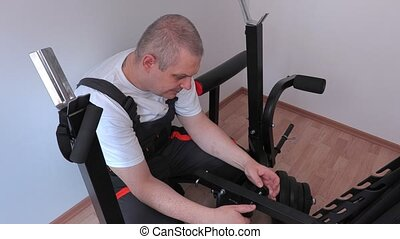 Worker fixing bolts on exercise machine