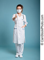 Confident female doctor or nurse wearing surgical mask -...