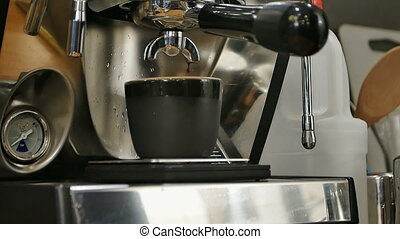Espresso pouring into a cup from professional machine. Close...
