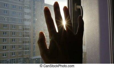 The female hand touches the sun and plays with the sun's rays