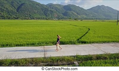 Aerial View of Woman Walking with Girl along Road by Rice...