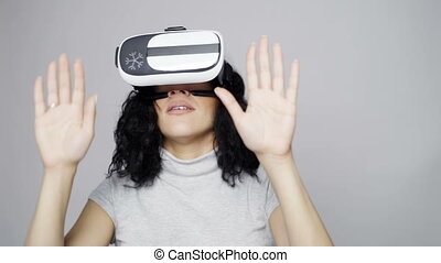 Woman wearing virtual reality goggles looking around...