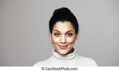 Closeup of young mixed race woman looking at camera smiling...