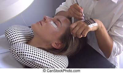 Professional master make long lashes holding out a pair of...