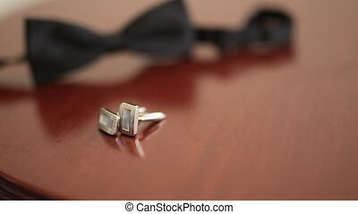 Black shoes of the groom, red bow tie, cufflinks, belt, on a...