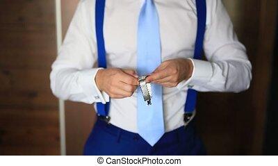 Man tying his tie. The groom tying his tie. Wedding groom...