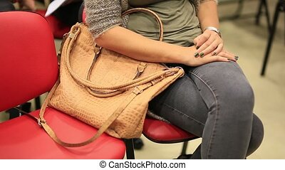 A girl is sitting on a chair with a bag in her hands