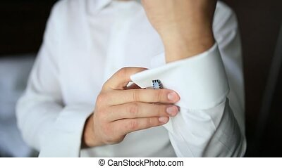 Buttoning cuffs. The groom wears cufflinks. Businessman...