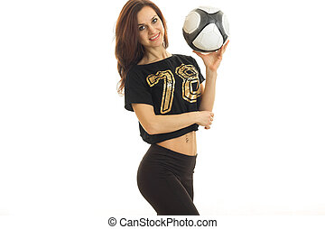 a charming young girl in sportswear is smiling and holding a soccer ball