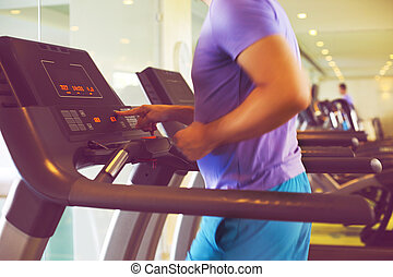 Healthy young man training on a treadmill in a sport center