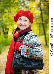 woman in autumn park - senior woman in coat at autumn park...