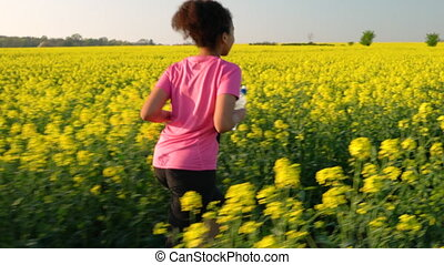 Mixed race teenager running or jogging in yellow flowers -...