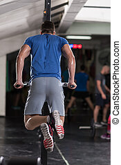 man doing exercises parallel bars - young muscular...