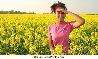 4K video clip of beautiful healthy mixed race African American girl teenager female young woman running or jogging in field of yellow flowers