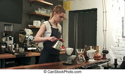 Young female barista in trendy modern cafe coffee shop pours...