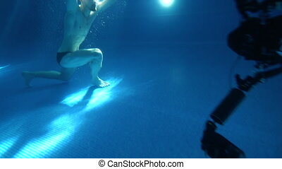 Behined the scenes. A young man somersaults and does a somersault under the water. He is posing in front of the camera. Underwater view.