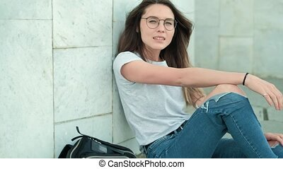 Girl brunette in glasses with a black backpack sits on a gray marble wall, straightens her hair and laughs, rejoices, the wind blows
