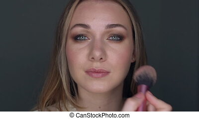 Attractive girl applying make up rouge. Cosmetic for skin...
