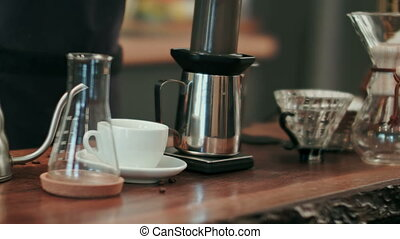 Barista pouring water on coffee ground with filter. Close...