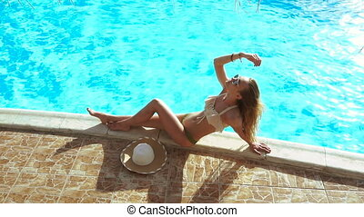 blonde lady in sunglasses and swimsuit lying and sunbathing...