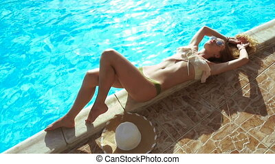 Fashion model in sexy swimsuit lying and sunbathing by the...