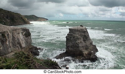 Seascape on background of horizon, clouds in sky and rocks New Zealand.