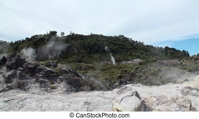 Geysers hot springs on background of forest and sky horizon...