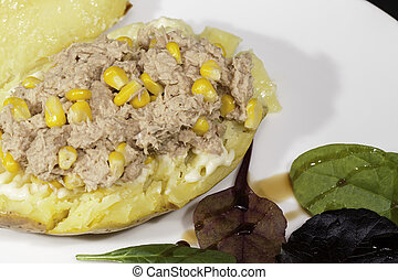 Healthy low calorie meal of tune sweetcorn baked potatoe with salad