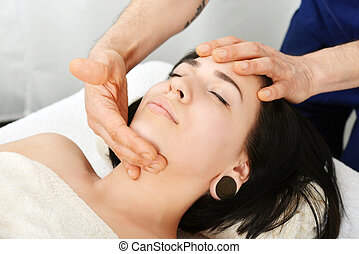 Face massage - Young attractive woman getting face massage...
