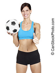 Confident athletic young woman with a soccer ball showing a thumbs up sign on white