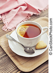 Cup of tea with lemon and cookies in shape of heart on tray...