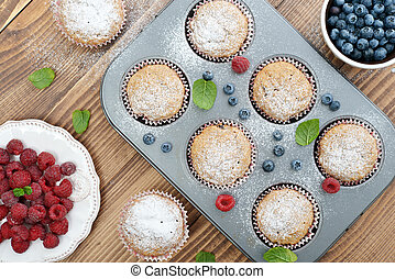 Just Baked  Muffins In Bakeware with fresh berries, top view
