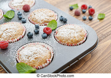 Just Baked  Muffins In Bakeware with fresh berries closeup